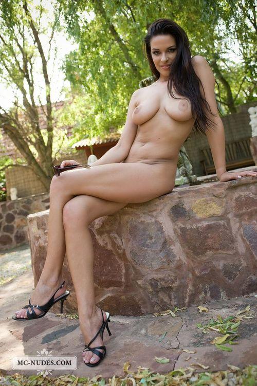Симпатичная обнаженная девушка у фонтана
