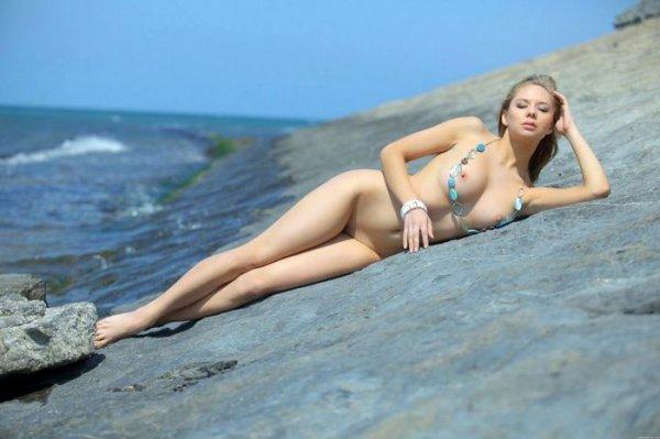 Симпатичная блондинка обнажается у воды эротика