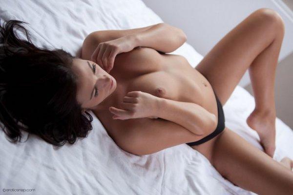 Симпатичная девушка эротично позирует на кровати