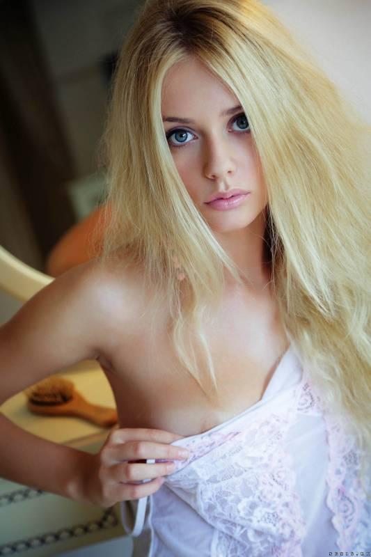 Красивая блондинка эротично позирует на кровати