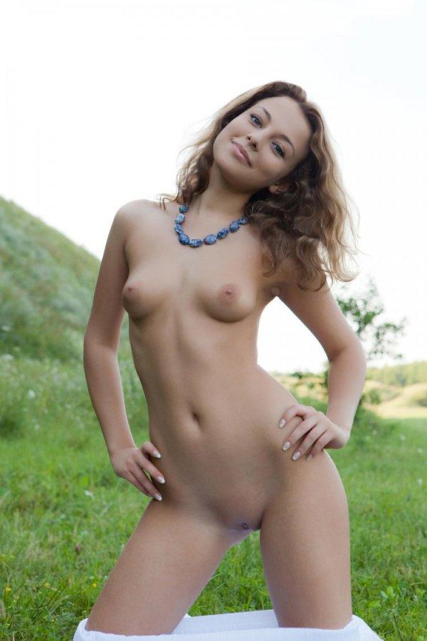 Симпатичная девушка голой позирует на зеленом поле