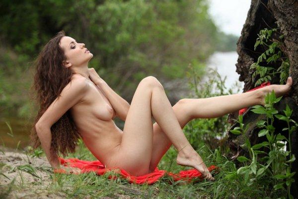 Симпатичная девушка в красном платье показывает свое голое тело