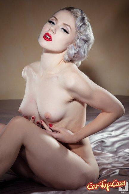 Прекрасная белая девушка позирует на кровати