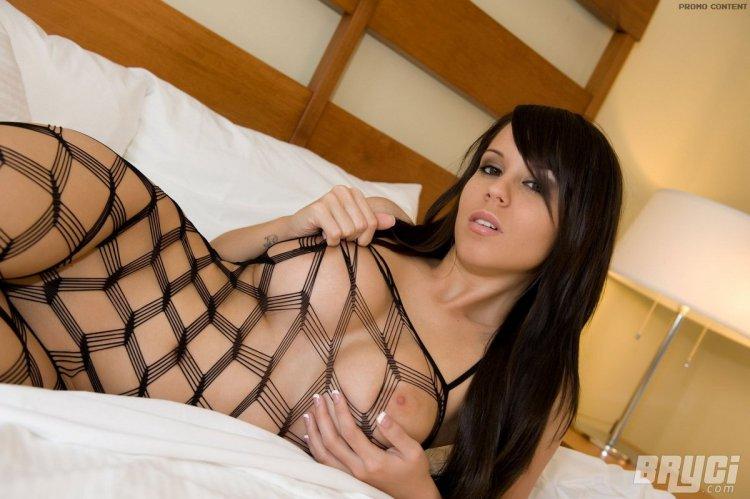 Дева bruci позирует на кровати показывая свою сексуальную фигуру и большие сиськи